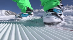 SLOW MOTION CLOSE UP: Extreme snowboarder riding on groomed snow in ski resort Stock Footage
