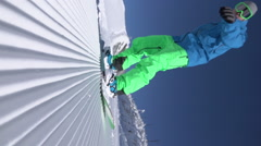 VERTICAL SLOW MOTION: Extreme snowboarder riding on groomed snow in ski resort Stock Footage