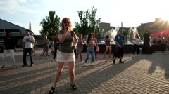 Girl teaches people how to dance salsa, at sunset on the square Arkistovideo