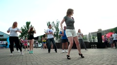 Girl teaches salsa grppu people on the street Stock Footage