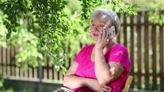 Blonde woman sits on the chair in garden and talks on smartphone Stock Footage