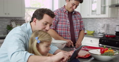 Girl using tablet in kitchen with male parents, close up, shot on R3D Stock Footage