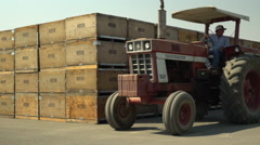 Tractor Slow Mo driving by raisin bins Stock Footage