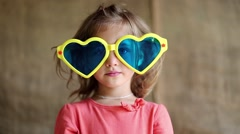 Little girl in big sun glasses in the shape of hearts looks at the camera Stock Footage