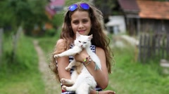 Beautiful girl holds in hands white cat and looks at the camera Stock Footage