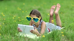 Attractive girl in big sunglasses with tablet computer lies on green grass Stock Footage