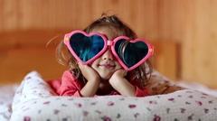 Little girl in big glasses in the shape of hearts lies on the bed Stock Footage