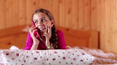 Girl with red smartphone lies on the bed Stock Footage