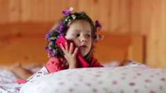 Little girl with a wreath on his head and with red smartphone lies on the bed Stock Footage