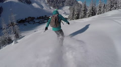 Female snowboarder riding fresh powder snow towards idyllic Austrian town resort Stock Footage