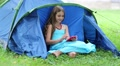 Beautiful girl sits on grass near tourist tent and uses smartphone HD Footage