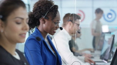 4K Portrait smiling customer service operator taking calls in busy call center Stock Footage