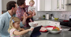 Girl uses tablet in kitchen with parents, dad holding baby Stock Footage
