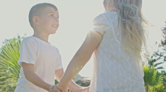 Happy boy and girl dancing in sunlight. Slow motion Stock Footage