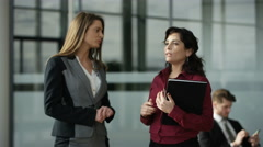 4K Businesswomen talking shake hands in crowded area of large modern office Stock Footage