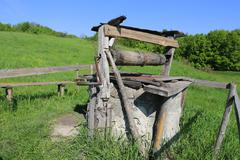 Old draw well on green meadow Stock Photos