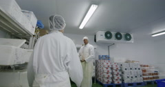 Workers packing boxes of fresh fish in a seafood processing factory Stock Footage