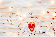 Christmas and New Year 2017 background. Red heart, light bulbs and confetti o Stock Photos