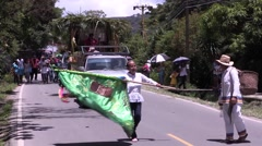 Woman waiving handsewn flag leading parade down street Stock Footage