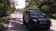 Black police car with lights on sitting in street during parade Stock Footage