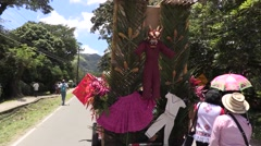 Panamanian crowd following decorated cart with evil monster puppet on back Stock Footage