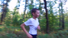 Slim teenager boy is running on paths and trails in the forest. Stock Footage