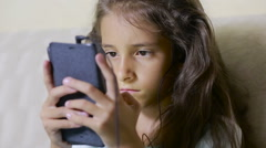 Girl child with a cell phone browses the Internet. headphones Stock Footage