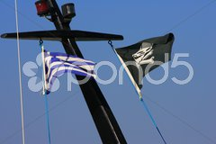 Pirate flag flying from a ship's mast. Stock Photos