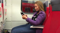 Young beautiful girl use a tablet computer sitting in a subway car Stock Footage
