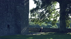 4k Medieval Shot of Game of Thrones Style Queen Walking between Castle and Tree Stock Footage