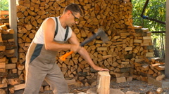Young man lays on chopped wood in the woodpile Stock Footage