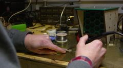 Man soldering wire to a circuit board, close up of hands, shot on R3D Stock Footage