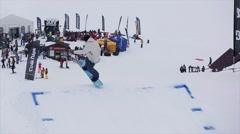 Snowboarder in helmet jump from springboard. Snowy mountains. Ski resort. Crowds Stock Footage