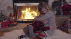 Little Girl Hugs Her Younger Brother By Cozy Fireplace, Decorated For Christmas Stock Footage