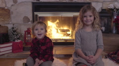 Brother And Sister Sit By Cozy Fireplace, They Smile At Camera And At Each Other Stock Footage