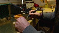 Man working on a circuit board with soldering iron, close up, shot on R3D Stock Footage