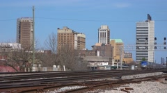 The City Of new Orleans passenger train leaves Birmingham, Alabama with the city Stock Footage