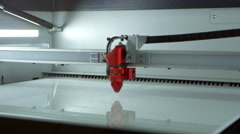 A laser cutter in operation at a 3D printing lab, shot on R3D Stock Footage