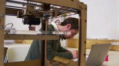 Designer working beside a 3D printer in a design studio, shot on R3D Stock Footage