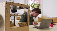 Designer drawing in a 3D print studio and checking computer, shot on R3D Stock Footage