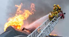 Firefighters battle blazing house fire Stock Photos