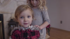 Sister Decorates Her Younger Brother With Silver Garland, Like A Christmas Tree Stock Footage