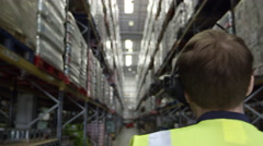 Camera follows man locating stock in warehouse, shot on R3D Stock Footage