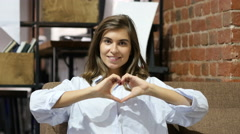 Heart Shape with HAnds by Young Lovely Girl Sitting on Sofa Stock Footage