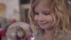 Little Girl Is Mesmerized By Snow Globe, She Watches Intently, Then Smiles Stock Footage