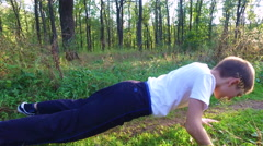 Slim teen boy is wrung out off the ground in the forest. Stock Footage