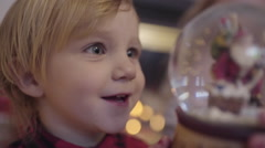 Excited Little Boy Watches Snow Globe, He Sees Santa And Shows His Sister Stock Footage