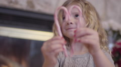 Little Girl Makes A Heart With Candy Canes, Smiles With Excitement Stock Footage