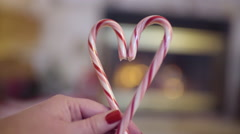 Woman With Red Nails, Holds Two Candy Canes Together To Create A Heart Shape Stock Footage