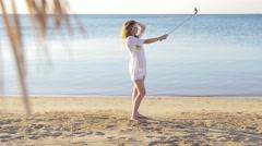 Happy girl making a selfie near the sea. HD Stock Footage